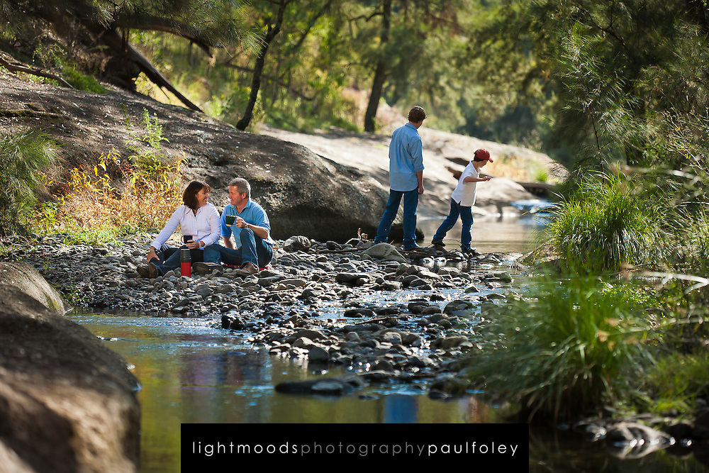 Family relaxing and playing beside an Australian Creek called The Washpools in Towarri National Park near Scone, NSW, Australia.