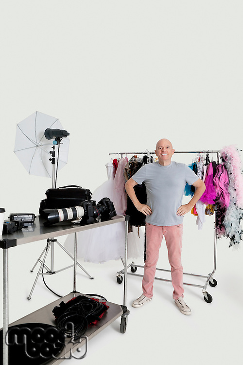 Portrait of senior man with hands on hips standing in front of clothes rack and photographic equipments in studio