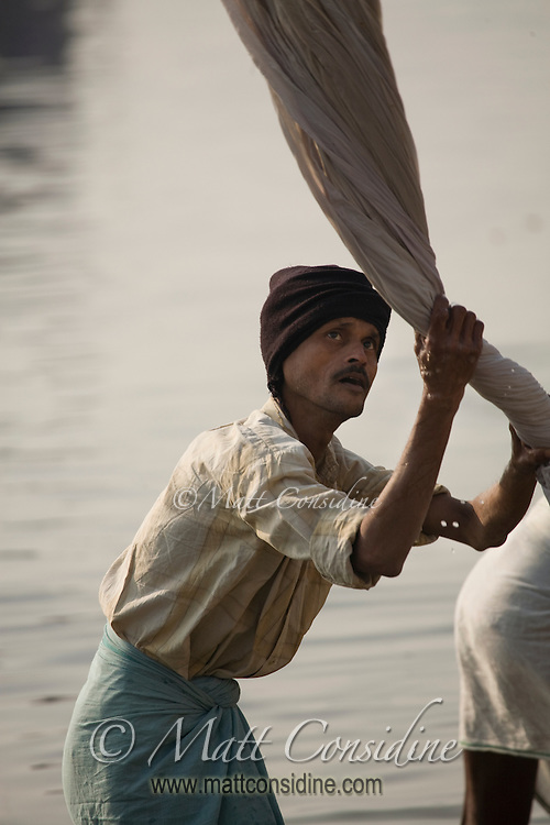 A washerman (dhobi wallah) washing clothes on the bank of River Ganga in Varanasi.<br /> (Photo by Matt Considine - Images of Asia Collection)