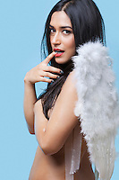Portrait of sensuous young woman wearing artificial wings over blue background