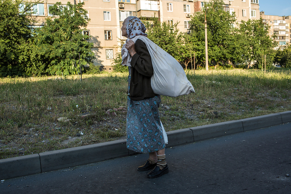 A woman carries belongings to a shelter on Tuesday, July 29, 2014 in Donetsk, Ukraine.
