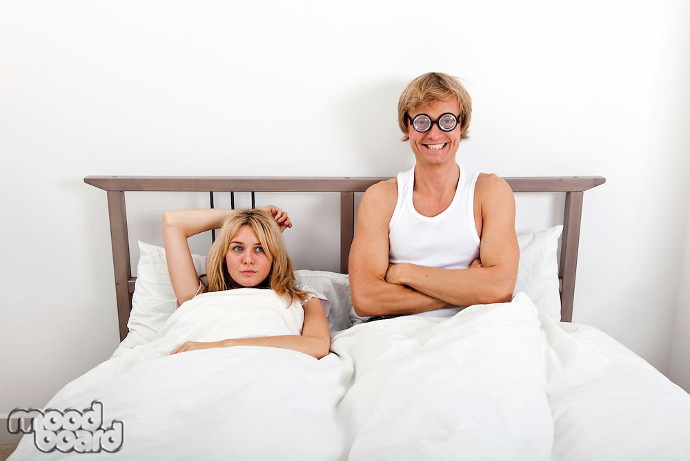 Portrait of happy man wearing retro glasses while sitting with woman in bed