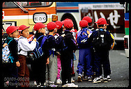 Red-capped schoolboys push in a line as they file onto bus to go to school; Mishima. Japan