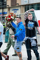 The English Defence League (EDL) return to Sheffield to lay flowers at Sheffield War Memorial which is fenced off to stop counter protesters occupying the whole of Barkers Pool. EDL leader Tommy Robinson strides into Barkers Pool holding up his floral tribute<br /> <br /> 8 June 2013<br /> Image © Paul David Drabble<br /> www.pauldaviddrabble.co.uk