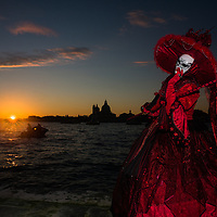 Masked person by the Grand Canal at dusk during the carnival of Venezia