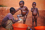 "12-03-21   -- KAMPALA, UGANDA --  Fiona Makumungu, 12, bathes brother Silas, 3, as Maxson, 3, waits his turn in the Acholi Quarter on March 21, 2012. Mother Pricilla Akumu says she would go back to northern Uganda if she had the means. ""God, if you help me, I will go back.""  Photo by Daniel Hayduk"