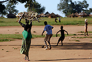 October 6, 2006 - A woman carries firewood as children play soccer in Coope camp for internally displaced people, or IDP, near Gulu in north Uganda. Coope, with a population of 18,000, is one of 76 IDP camps around Gulu, the main base for the Uganda Peoples Defense Force fighting the insurgent Joseph Kony's Lord's Resistance Army. Kony's LRA movement has been fighting for the past 20 years to force the East African country to be ruled according to the Christian Ten Commandments. Over 2 million people, mostly of the Acholi tribe, have moved or were forced to move from their villages to camps close to the towns of Gulu, Lira, and Kitgum where they are watched over by the Ugandan Army. The LRA rebels have abducted thousands of children and have forced them to fight against the Ugandan Army and the Acholi people. Current peace talks between Kony's LRA and the Ugandan government held in Juba, southern Sudan, offer a glimpse of hope to ending this ongoing conflict..(Photo by Jakub Mosur/Polaris)<br />