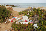 Pile of waste left in nature defacing the landscape and polluting the environment on a beach
