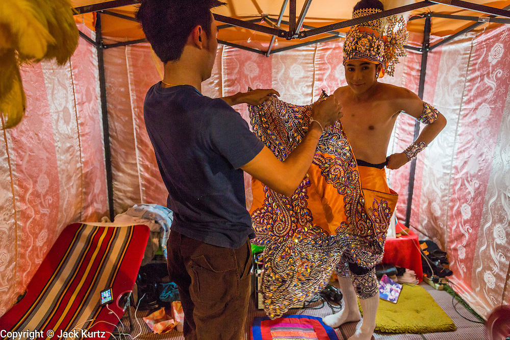 22 NOVEMBER 2013 - BANGKOK, THAILAND: A performer with the Prathom Bunteung Silp mor lam troupe puts on his costume before a show in Bangkok. Mor Lam is a traditional Lao form of song in Laos and Isan (northeast Thailand). It is sometimes compared to American country music, song usually revolve around unrequited love, mor lam and the complexities of rural life. Mor Lam shows are an important part of festivals and fairs in rural Thailand. Mor lam has become very popular in Isan migrant communities in Bangkok. Once performed by bands and singers, live performances are now spectacles, involving several singers, a dance troupe and comedians. The dancers (or hang khreuang) in particular often wear fancy costumes, and singers go through several costume changes in the course of a performance. Prathom Bunteung Silp is one of the best known Mor Lam troupes in Thailand with more than 250 performers and a total crew of almost 300 people. The troupe has been performing for more 55 years. It forms every August and performs through June then breaks for the rainy season.     PHOTO BY JACK KURTZ