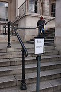 A woman carefully descends steps, with an Exit Only sign on the steps of the National Gallery, on 11th January 2017, in Trafalgar Square, London, England.