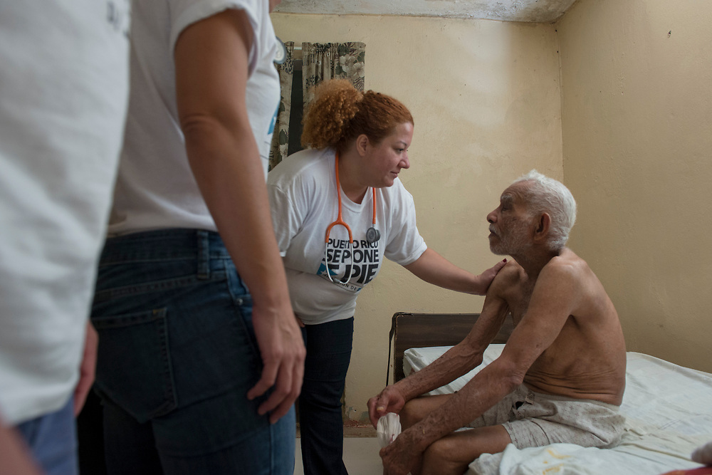 Comerio, PR, November 11, 2017--Dr. Lourdes Marrero with Mission de Haiti Se Pone de Pie checks on  94-year-old  Pedro Andino in his home in La Verde, PR. Medical teams made house visits in Comerio and surrounding neighborhoods to check on the elderly and sick.  Photo by Lori Waselchuk/BAF