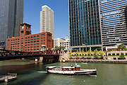 A sightseeing boat along the Chicago River looking toward North Clark Bridge, Reid Murdoch Building and skyline during summer in Chicago, Illinois, USA