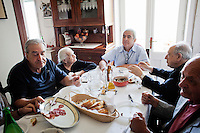 "PERDASDEFOGU, SARDINIA, ITALY - 30 JUNE 2013: The Melis family and their guest have lunch togeter to celebrate the 100th birthday of Claudina Melis (second from left) in Perdasdefogu, Italy, on June 30th 2013.<br /> <br /> Last year, the Melis family entered the Guinness Book of World Records for having the highest combined age of any nine living siblings on earth — today more than 825 years. The youngest sibling, Mafalda – the ""little one"" – is 79 years old.<br /> <br /> The Melis siblings were all born in Perdasdefogu to Francesco Melis and Eleonora Mameli, who had a general store. Consolata, 106, is the oldest, then Claudia, 100; Maria, 98; Antonino, 94; Concetta, 92; Adolfo, 90; Vitalio, 87; Fida Vitalia, 81; and Mafalda, the baby at 79. Their descendants now account for about a third of the village."