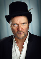 This portrait featuring Ian Puleston-Davies witch doctor style top hat with feather. An intense portrait with a sinister look of a man possessed.