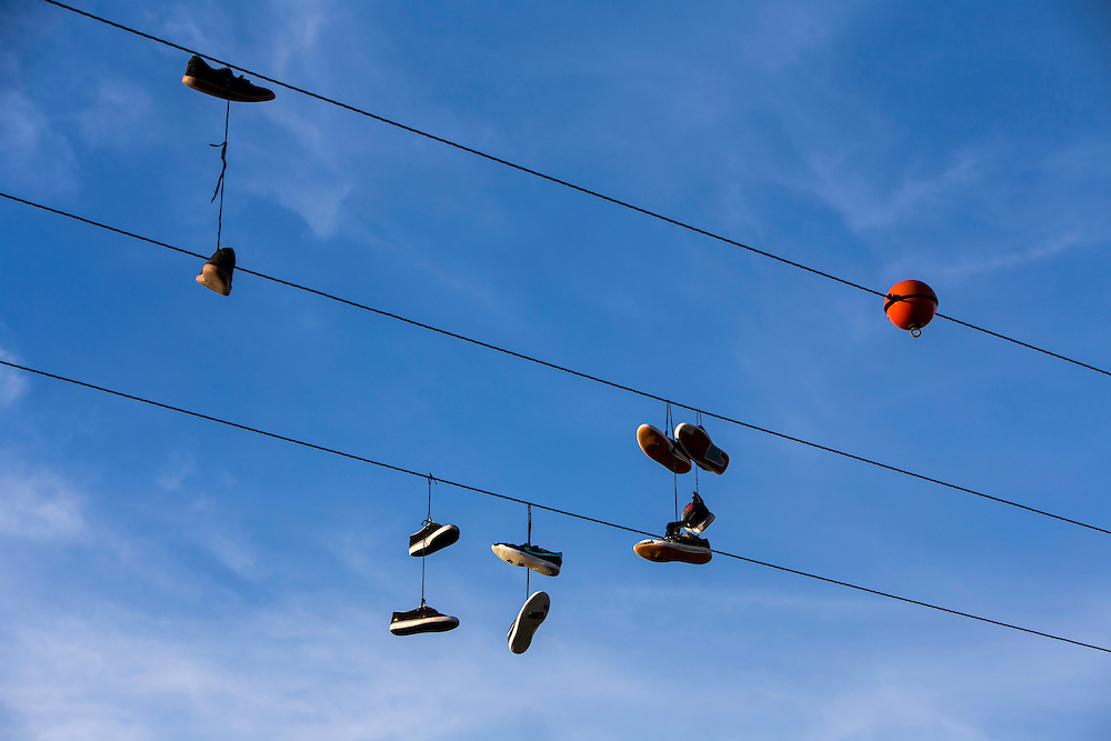 Pairs of shoes hanging on a wire. Wadebridge, Cornwall. UK Shoe tossing, the act of using shoes as projectiles is a constituent of a number of folk sports and practices. The act of throwing a pair of shoes onto telephone wires, powerlines, or other raised wires.