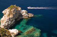 A speedboat passing limestone cliffs on the sout coast of Paxos, Ionian Islands, Greece