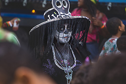 London, August 28th 2016. A woman, her face painted like a skull passes through the crowd as Europe's biggest street party, the Notting Hill Carnival gets underway.