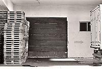 Paller står stablet opp ved en garasjeport på hurtigrutekaia i Ålesund. <br /> Foto: Svein Ove Ekornesvåg