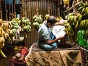 11 NOVEMBER 2014 - SITTWE, MYANMAR: A banana merchant reads the newspaper in his shop in the banana market in Sittwe, Myanmar. Sittwe is a small town in the Myanmar state of Rakhine, on the Bay of Bengal.   PHOTO BY JACK KURTZ