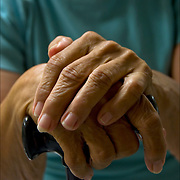Close up of elderly woman's hand resting on walking cane.