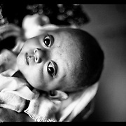 An abandoned ethnic Karen baby looks up as it is held at the Mae Tao clinic in Mae Sot, Thailand(Photo by David Longstreath)