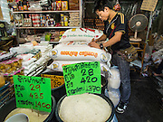 """13 FEBRUARY 2014 - BANGKOK, THAILAND: A market vendor sells rice in Khlong Toei Market in Bangkok. The Thai government instituted a """"rice pledging scheme"""" after the election in 2011. The government agreed to buy farmers' rice crops at above market prices then planned to warehouse the rice and sell it on international markets when prices recovered. At the same time, India and Vietnam started to export large quantities of rice and the Thai government fell short of funds to pay for rice it had already purchased from farmers. Many farmers have not been paid for rice grown in 2013 and some of the rice in the Thai warehouses is allegedly rotting. Thailand has fallen from number 1 rice exporter in the world to number 3 and several government to government contracts the Thais signed with rice importing countries (like China) have been cancelled. Farmers, once key supporters of the government are now joining anti-government protests in Bangkok and occupying government ministries including the Ministry of Commerce.    PHOTO BY JACK KURTZ"""