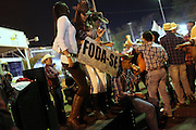 Cowgirls hold a banner reading Fuck off as they dance at the amusement park set aside the  Barretos Rodeo Festival in the city of Barretos, Brazil, Thursday, Aug. 23, 2012. The festival which gathers ten of thousands each year in August  is long awaited by cowboys, cowgirls and big sponsors related to the industry of meat, beer and leather. The festival has its origins in the transfer of cattle from pasturing in the nearby states of Minas Gerais, Goiás, Mato Grosso do Sul, and Mato Grosso to slaughterhouses in Barretos, still home to two of Brazil biggest protein transformation industries, JBS Friboi and Minerva.  Brazil is on a quick path to become a global power. Rising economy, big infrastructure projects, an emerging and eager consuming middle class and the booming national industry are the evidences and consequences of the wealth in the southern nation. But the often hidden source of all this wealth falls far from the luring Rio beaches or the Kolkata-New York mix that Sao Paulo is. Behind texan hats and a similar attitude the countrymen display their power through a myriad of projects, festivals and behavior visually analyzed here.