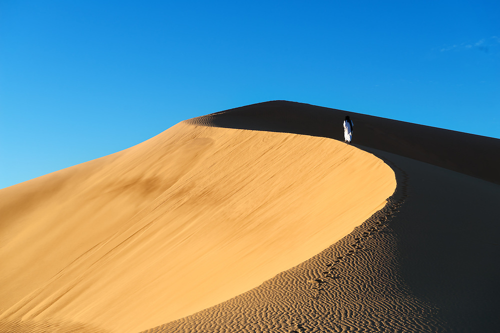A traditional dressed moroccan man walks up a sand dune, Sahara desert, Morocco.