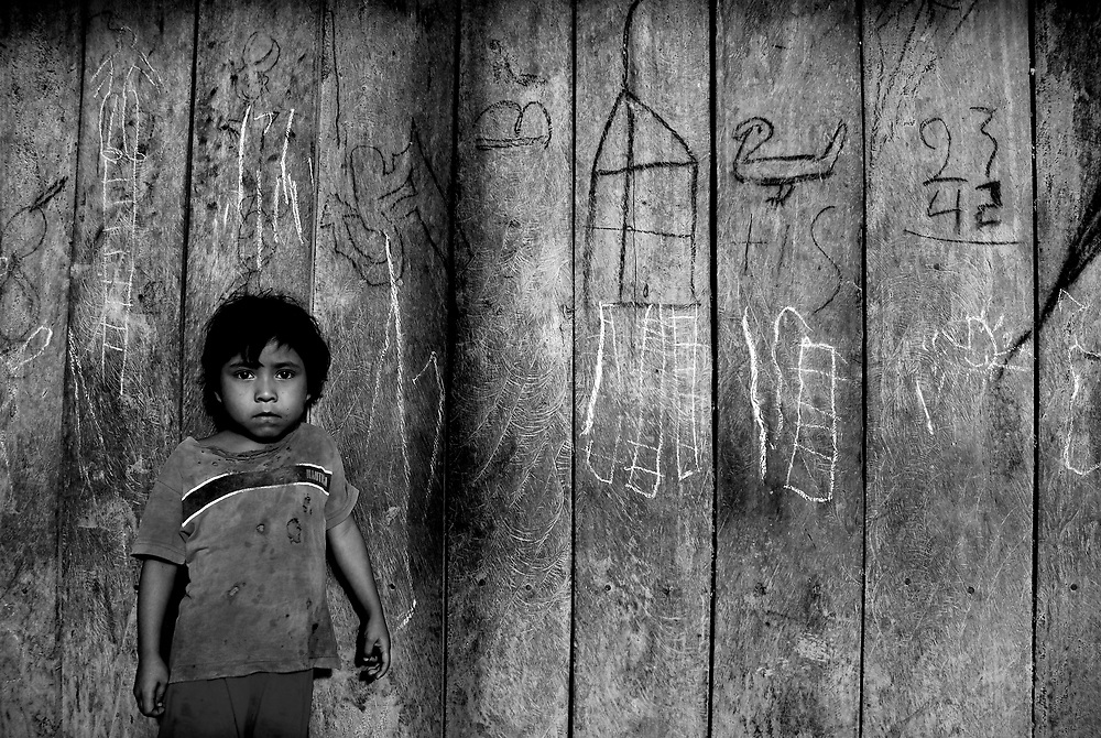 A child poses for a portrait outside of her family's living quarters in the La Esperanza Albergue for migrant sugarcane workers and their families in Tuxtepec, Mexico.