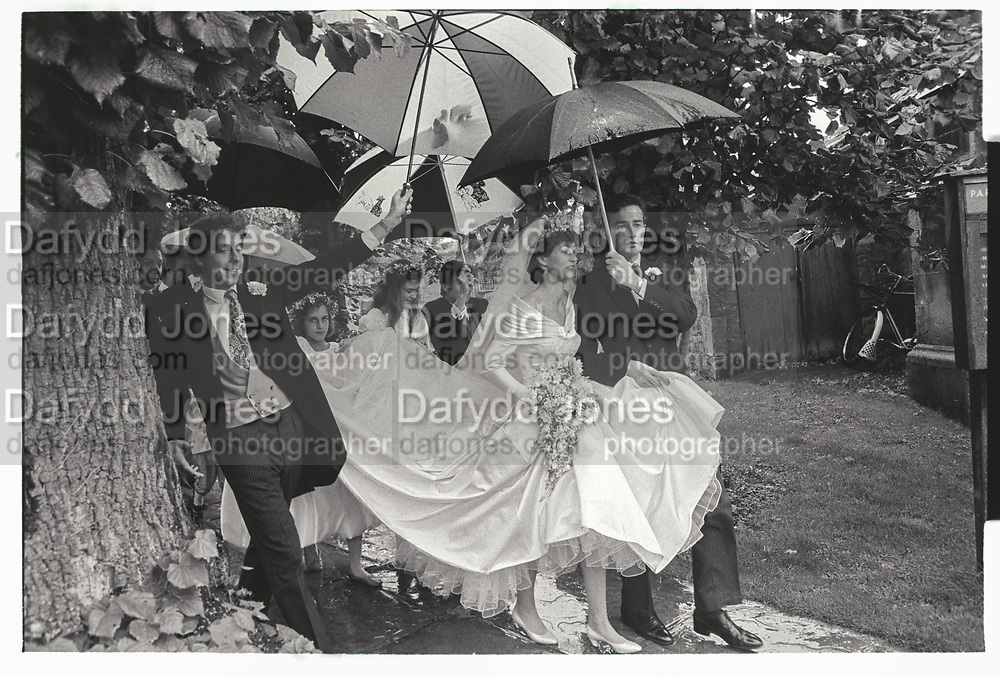 Anthony Brockbank on left, Arriving for their wedding in rain: Fiona Marr and Alexander Wilmot-Sitwell, Chipping Campden. 10 October 1987,