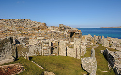 """The Broch of Gurness.  The Broch of Gurness is an Iron Age broch village on the northwest coast of Mainland Orkney in Scotland overlooking Eynhallow Sound. The remains of the central tower are up to 3.6 metres (11.8 ft) high, and the stone walls are up to 4.1 metres (13.5 ft) thick.The broch probably had a conical or mildly hyperbolic top,and has the remains of a settlement surrounding and adjoining it.<br /> <br /> Pieces of a Roman amphora dating to before 60 AD were found here, lending weight to the record that a """"King of Orkney"""" submitted to Emperor Claudius at Colchester in 43 AD.<br /> <br /> The broch is in the care of Historic Scotland.<br /> <br /> (c) Andrew Wilson   Edinburgh Elite media"""