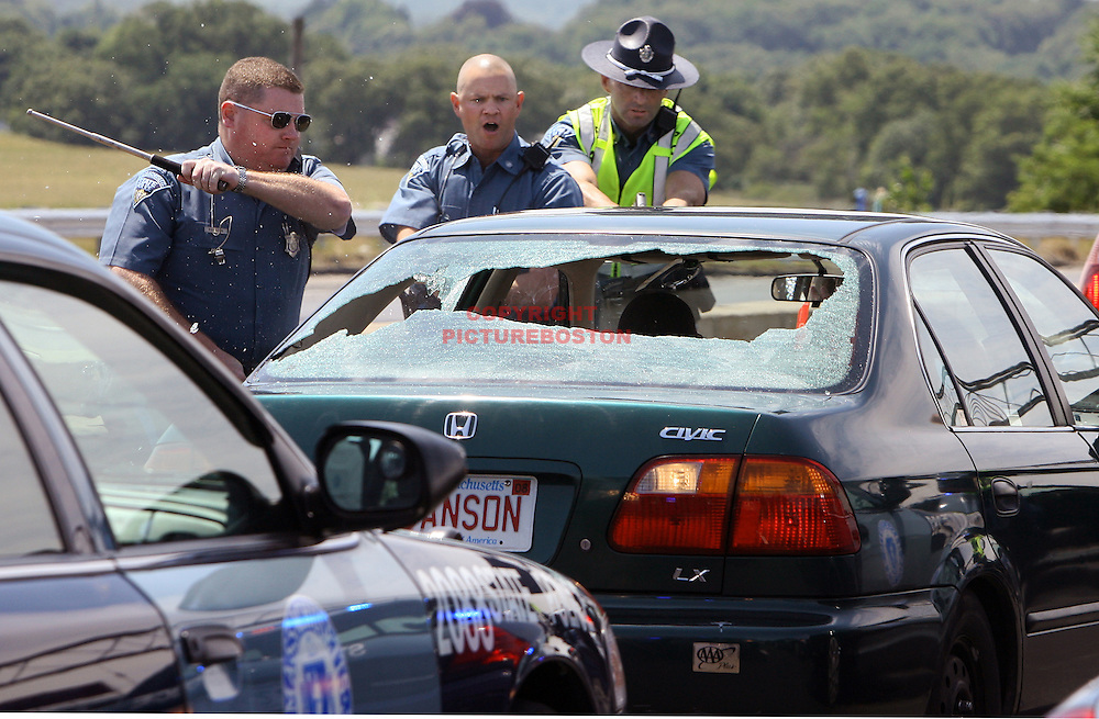 The driver backs into a police car as a Massachusett's state trooper breaks her windows.