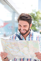 Happy man reading road map in city
