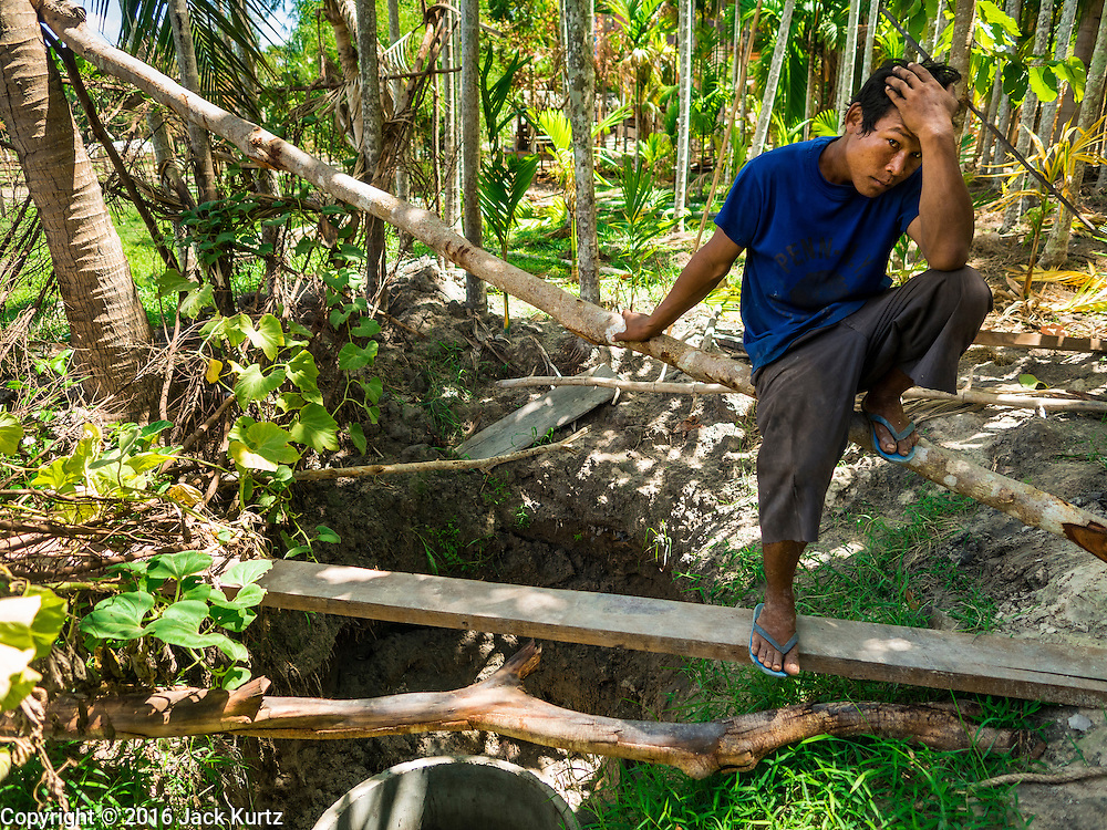 02 JUNE 2016 - SIEM REAP, CAMBODIA: NGOR, 33 years old, sits over his well while he refills the 3,000 litre water tank on his tractor. He sells water from his well in the villages around his home east of Siem Reap. Cambodia is in the second year of  a record shattering drought, brought on by climate change and the El Niño weather pattern. Farmers in the area say this is driest they have ever seen their fields. They said they are planting because they have no choice but if they rainy season doesn't come, or if it's like last year's very short rainy season they will lose their crops. Many of the wells in the area have run dry and people are being forced to buy water to meet their domestic needs.    PHOTO BY JACK KURTZ
