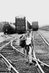 man with a bag over his shoulder walking along train tracks