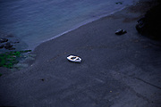 AJ02MF Small white dinghy boat alone on dark beach Lizard Point Cornwall England