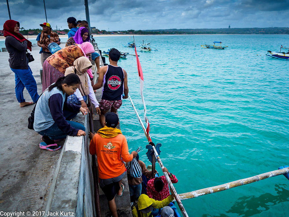 03 AUGUST 2017 - KUTA, BALI, INDONESIA:  Women wait on the jetty as their husbands from a trawler come back to shore on the jetty on Jimbrana Beach in Kuta. The beach is close to the airport and a short drive from other beaches in southeast Bali. Jimbrana was originally a fishing village with a busy local market. About 25 years ago, developers started building restaurants and hotels along the beach and land prices are rising. The new emphasis on tourism is changing the nature of the area but the fishermen are still busy very early in the morning.    PHOTO BY JACK KURTZ