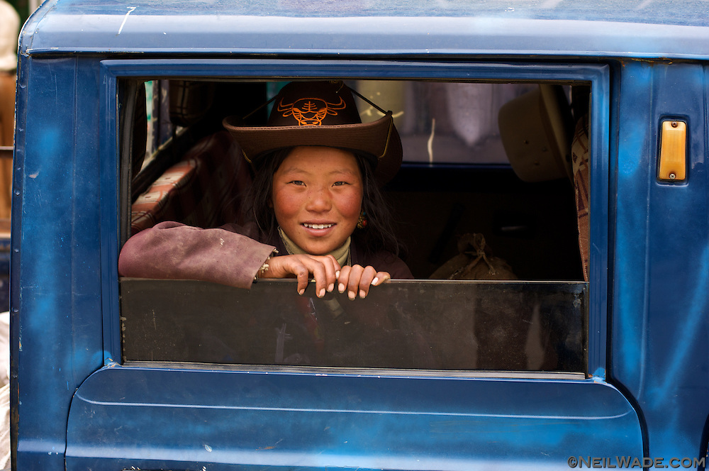 A Tibetan cowgirl peeks from behind a pickup truk's window in Litang, Tibet.