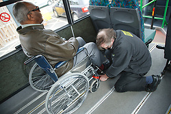 Bus driver securing wheelchair of visually-impaired wheelchair user on transport resource for people with physical and sensory impairment.