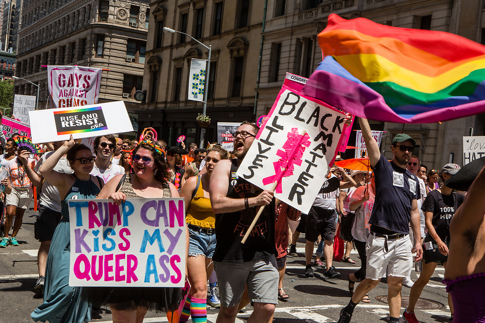 """New York, NY - 25 June 2017. New York City Heritage of Pride March filled Fifth Avenue for hours with groups from the LGBT community and it's supporters. Marchers from Rise and Resist with signs, including """"Trump can kiss my queer ass"""" and """"Black lives matter."""""""