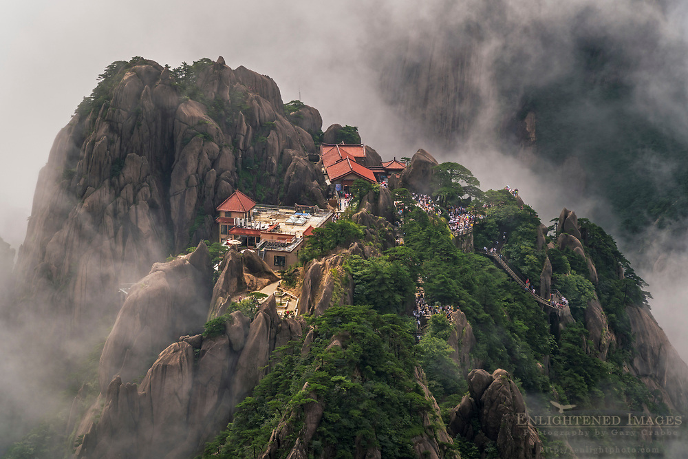 Tourists and guest house in rock outcrop and mist seen from Lotus Peak, in the Huangshan Mountains (Yellow Mountain), Anhui Province, China