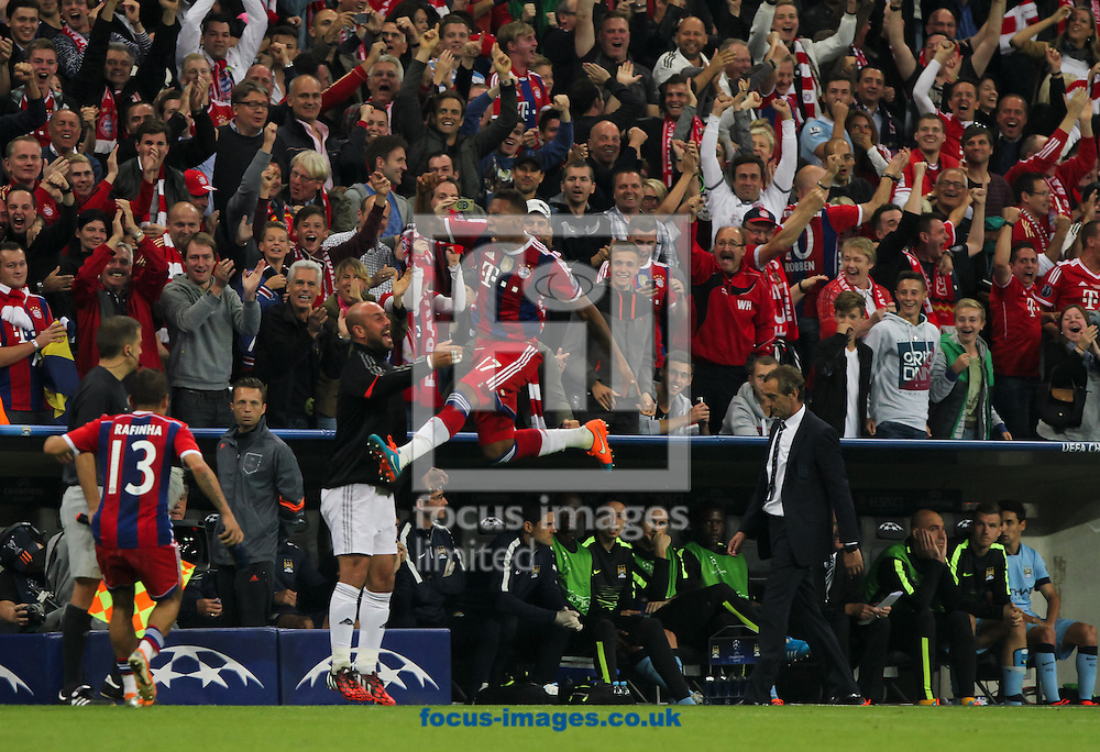 J&eacute;r&ocirc;me Boateng (centre) of Bayern Munich celebrates scoring his sides first goal as Manchester City manager Manuel Pellegrini and the Manchester City bench look dejected behind during the UEFA Champions League match at Allianz Arena, Munich<br /> Picture by Tom Smith/Focus Images Ltd 07545141164<br /> 17/09/2014