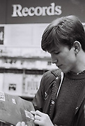 Friend checking a record in Our Price records, Ealing, UK, 1985.