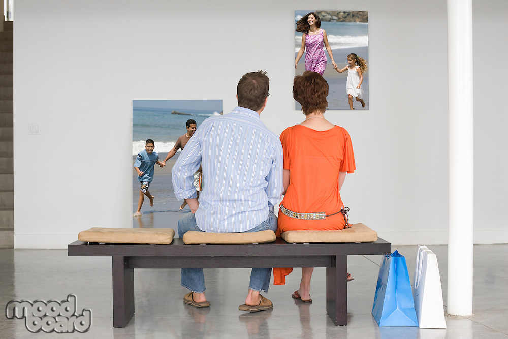Rear view of couple seated on bench looking at photographs representing future planning