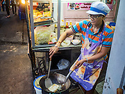17 JANUARY 2016 - BANGKOK, THAILAND:  A woman cooks an order at a food stand on Sukhumvit Soi 38, one of the most famous street food areas in Bangkok. Her family has operated a restaurant on the street for generations. The food carts and small restaurants along the street have been popular with tourists and Thais alike for more than 40 years. The family that owns the land along the soi recently decided to sell to a condominium developer and not renew the restaurant owners' leases. More than 40 restaurants and food carts will have to close. Most of the restaurants on the street closed during the summer of 2015. The remaining restaurants are supposed to close by the end of this week.           PHOTO BY JACK KURTZ