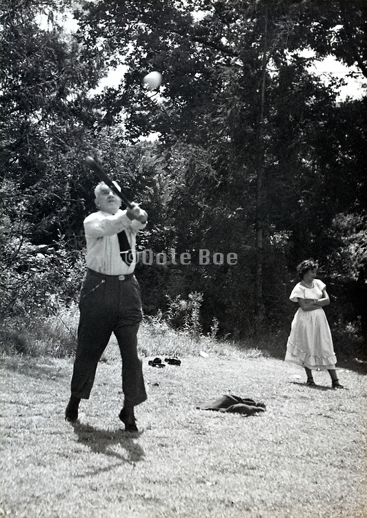 the boss swinging a baseball bat during a company sports recreational day USA 1940s