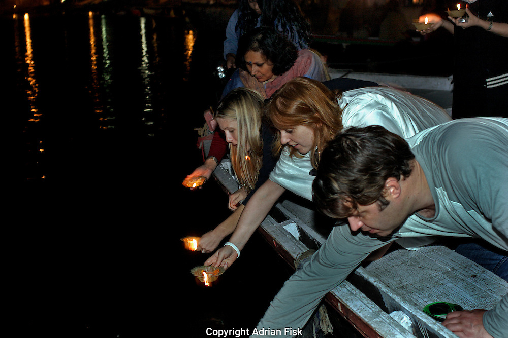 Marcel and members of Oxfam and place lighted candles in the river Ganges at Varanasi