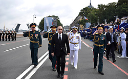July 30, 2017 - Saint Petersburg, Russia - July 30, 2017. - Russia, Saint Petersburg. - Russian President, Supreme Commander-in-Chief Vladimir Putin walks on the Admiralty Embankment in St. Petersburg ahead of the Main Naval Parade marking Navy Day. From left in the background: Western Military District Commander Colonel General Andrey Kartapolov, Russian Defense Minister Army General Sergey Shoigu and Russian Navy Commander-in-Chief Admiral Vladimir Korolyov. (Credit Image: © Russian Look via ZUMA Wire)