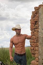 shirtless cowboy walking around an adobe wall in New Mexico