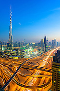 Dubai Downtown at twilight Sheikh Zayed Road and Burj Khalifa. Blue hour in the United Arab Emirates with major road junction illuminated by car light trails.